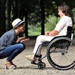 une femme en fauteuil face à une autre femme accroupie devant elle. Elles rient