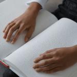 Livre en braille avec des mains qui lisent