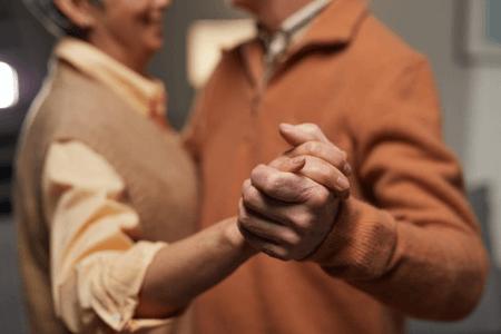 Couple de personnes agés qui danse main dans la main